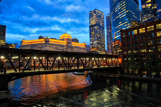 Chicago's illuminated night lights over Chicago River and at Merchandise Mart during rush hour.