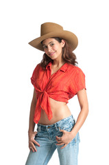 Pretty girl with a cowboy hat and bare midriff smiling at the camera. Isolated