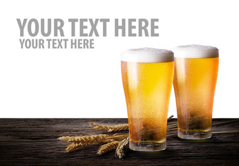 Cold beer with wheat on wooden table. Glasses of light beer on isolate white background with copy space.