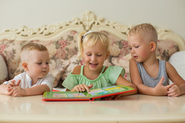 Little Boys and Girl Reading Book at Table at Home