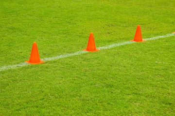 Orange cones on turf football or soccer green field, Training equipment..Soccer Football Training Session, Training Football on the Pitch,