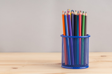 Colored pencils in the blue box on gray background