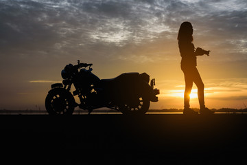 Silhouette of young woman biker take photo and motorcycle on the street at sunrise.Motorbike travel concept