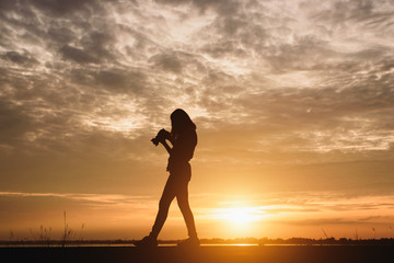 Silhouette young woman photographing landscape . Female photographer holding a camera at sunset