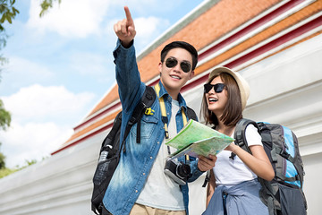Happy Asian couple tourist backpackers traveling on holidays in  Bangkok, Thailand
