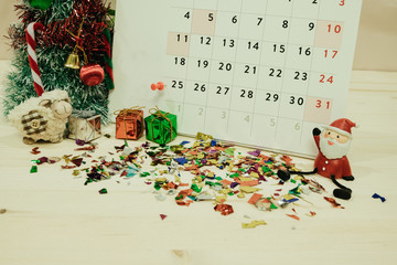 calendar with christmas day decoration equipment placed on wooden table included santa claus, christmas tree, gift boxes, paper. image for christmas event, happy new year, festival concept