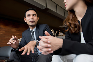 Asian man and woman discussing busniness details in a cafe lounge