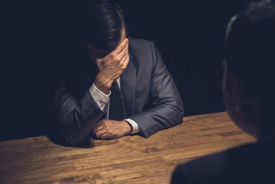 Suspect businessman displaying regret  in dark interrogation room