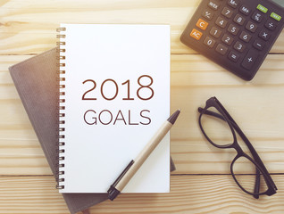"Inspirational motivating quote ""2018 goals""on notebook, pen, glasses and calculator on wooden table background with vintage filter."