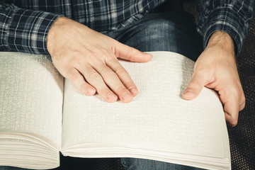 The blind man was reading a book written on Braille. Touch your finger on the braille code. A book with Braille text