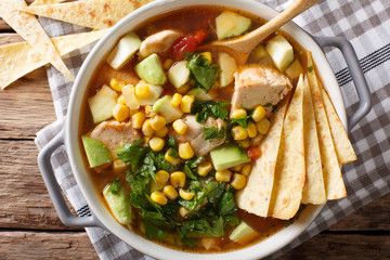 spicy tortilla soup with chicken, cilantro, tomatoes, avocado and corn close-up. horizontal top view