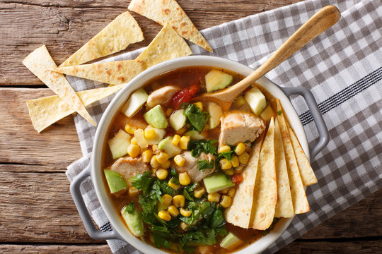 Mexican food: tortilla soup with chicken, tomatoes, avocado and corn close-up. horizontal top view