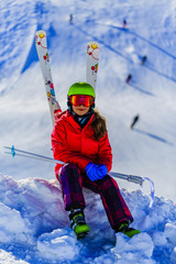 Portrait of happy young girl sitting in the snow with ski in winter time, ski slope in the background.