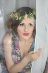 Beautiful dreamy young woman wih flove wreath  trough window glass