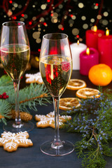 Champagne glasses in holiday setting. Christmas and New Year celebration with champagne. Christmas holiday decorated table with white sparkling wine, vertical