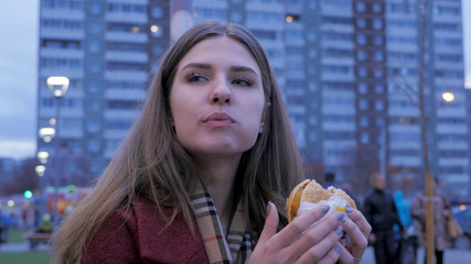 Young woman standing in an urban street and eating burger. Young woman eating fast food standing on the street