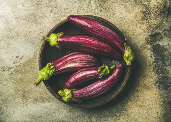 Flat-lay of fresh raw Fall harvest purple eggplants or aubergines in wooden bowl over grey concrete stone background, top view. Healthy Autumn vegan cooking ingredient