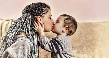 The little son kisses his mother.
