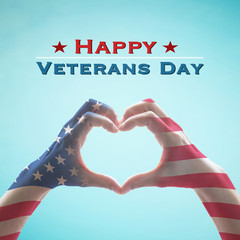 USA Happy veterans day with United Stated of America flag pattern on people's hands in heart shape on blue sky greeting announcement honoring all veterans who served American country