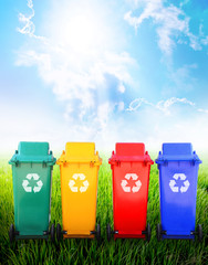 Colorful recycle bins in nature background.