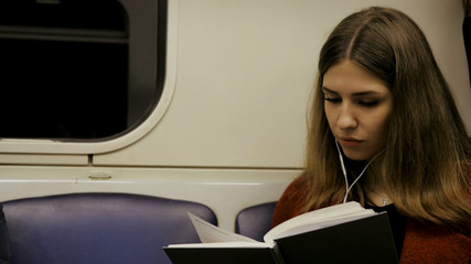 Young beautiful woman sitting on subway reading a book - commuter, student, knowledge concept. Young woman in the subway reading a book