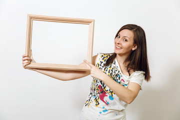 Portrait of a happy smiling brown-haired woman standing and holding empty wooden frame on the white background. With place for text for advertising.