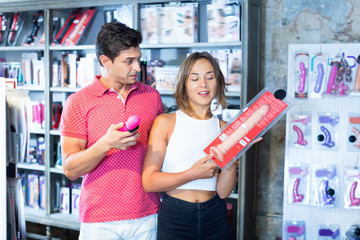 male and female purchasers touching big dildo in the modern sex shop