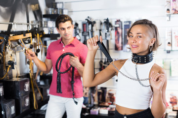 Portrait of positive girl and man n the sexshop