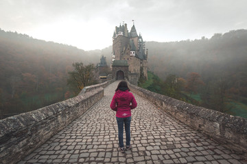 Woman in front of Burg Eltz, Germany, on a cold autumn morning