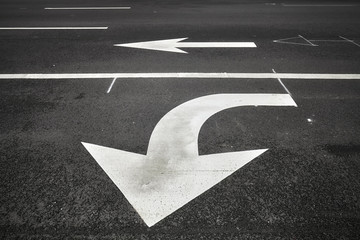 Turn or go straight street signs on asphalt, arrow pointing at viewer, conceptual background with focus on the first arrow.