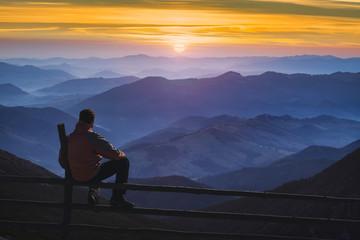 Man hiker sitting on a fence and enjoying the sunrise