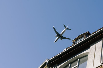 Airplane flying low above buildings, approach to landing