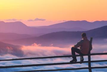 Man on a fence enjoying the sunset
