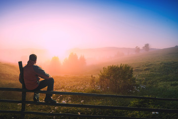 Man sitting on a wooden fence enjoy the misty morning
