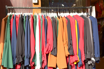 Rack of colourful clothes at market stall on Mile End Road in Whitechapel London England