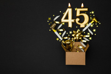 Number 45 gold celebration candle and gift box background