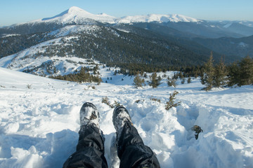 legs of the traveler in hiking boots with snow gaiters in the snowy mountains