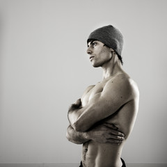 Handsome boy with naked torso and woolen cap