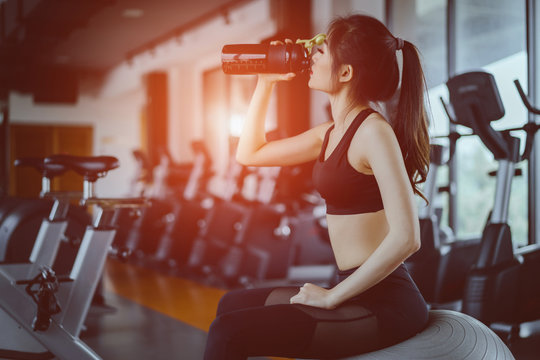 Young asian woman drinking protein shake from bottle after workout exercise for muscle at fitness gym healthy lifestyle bodybuilding sitting on yoga ball