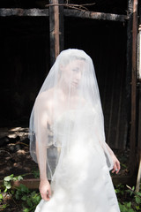 Young bride in the urban decay environment of Platt's Eyot Island in Hampshire UK