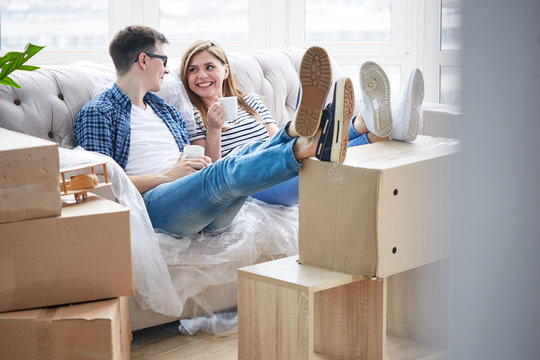 Joyful young couple sitting on sofa covered with plastic wrap, enjoying fragrant cappuccino and chatting animatedly with each other, interior of messy new apartment on background