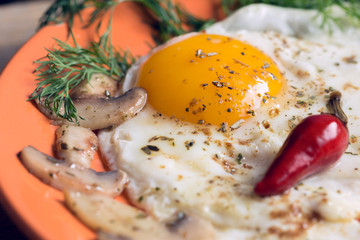 Fried egg with champignons, dill and red chili pepper