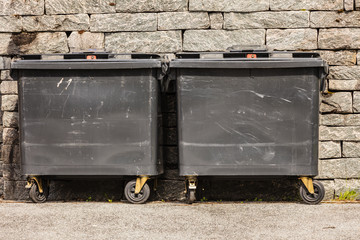 Two black industrial trash cay containers littler garbage