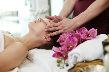 Side view portrait of beautiful young woman enjoying face lifting massage lying on table in SPA center and relaxing with male masseuse rubbing her temples
