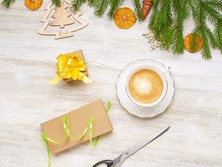 Wrapping gifts at the feast. Top view Cup of coffee, scissors, box, gift, ribbon on a light wooden background.