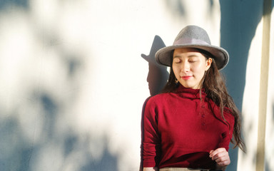 Pretty Chinese young woman stand in warm sunshine with shadows on wall.