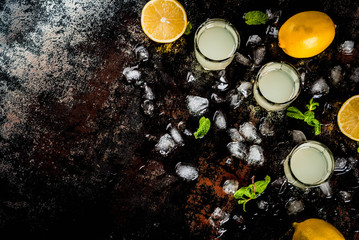Traditional italian alcoholic homemade beverage, lemon liqueur limoncello with fresh citrus, ice and mint, on rusty black table, copy space top view