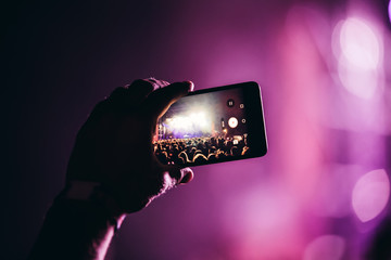 Close-up picture of person holding camera on music festival