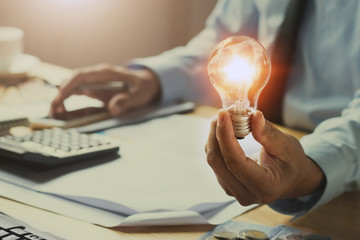 hand man accountant holding light bulb, new idea with innovation concept