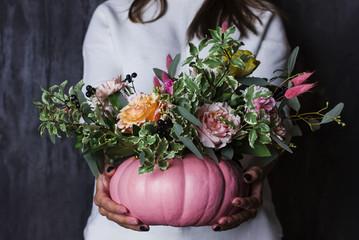 Autumn floral bouquet in pumpkin vase. Decoration of flowers in woman hands
